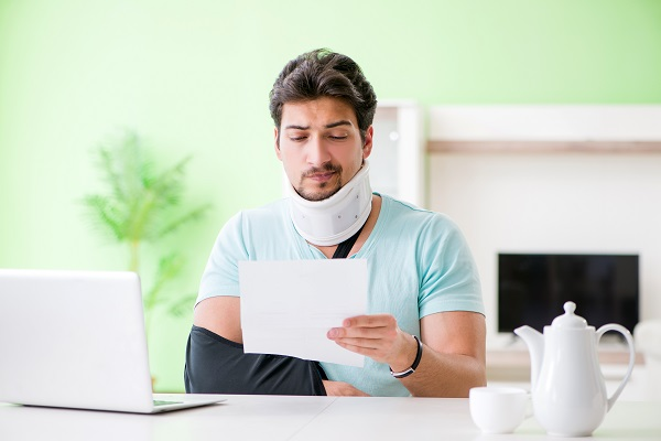 Man with injured arm and neck looking at his hospital bills and wondering, 'should I hire a personal injury lawyer?'