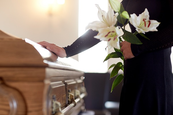 Woman touching casket with flowers in hand